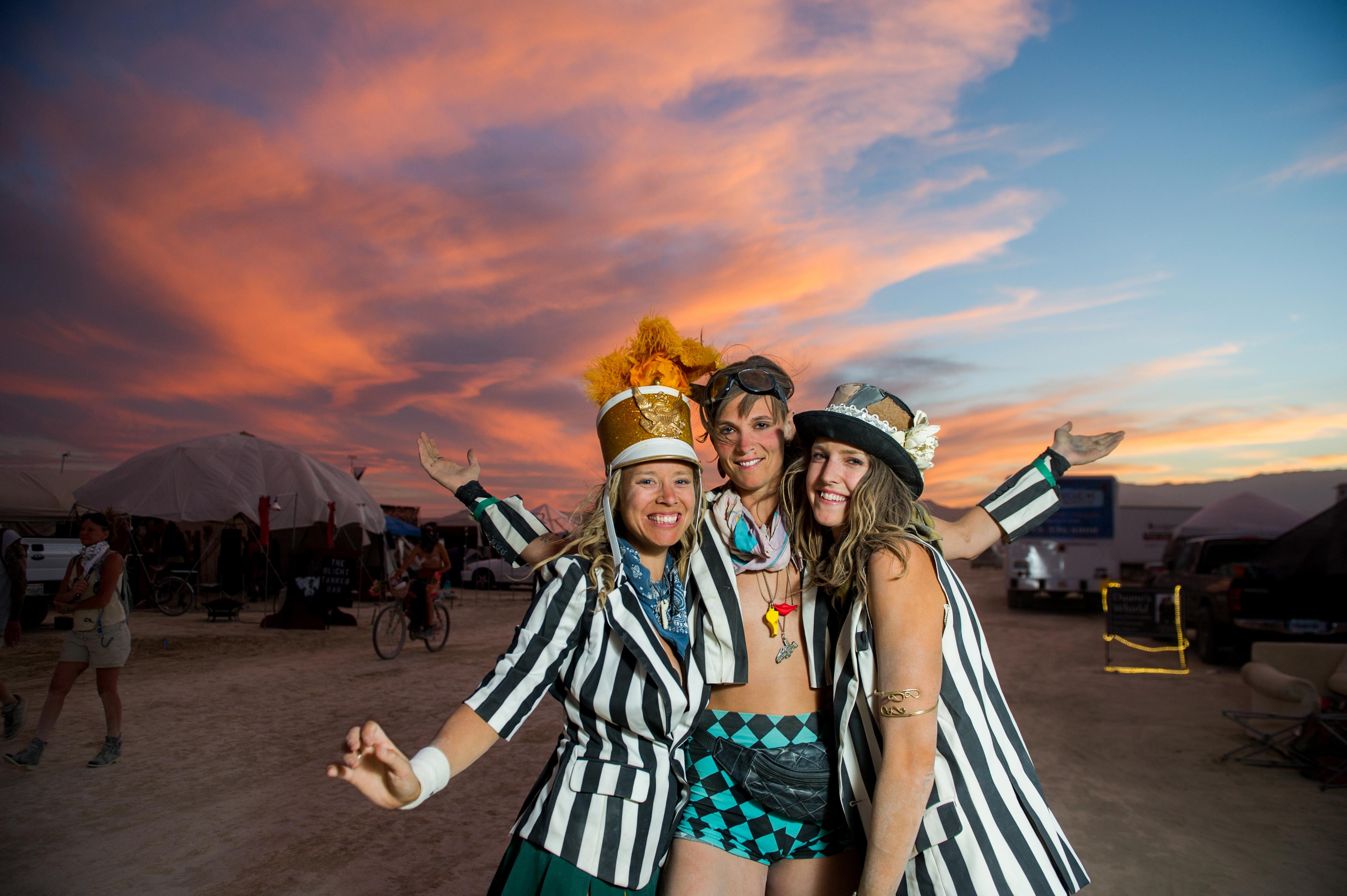 Burning Man, Black Rock City, Nevada, USA. Picture Stuart Walmsley. Sara, Izzy and Saxony enjoy a spectacular desert sunset.