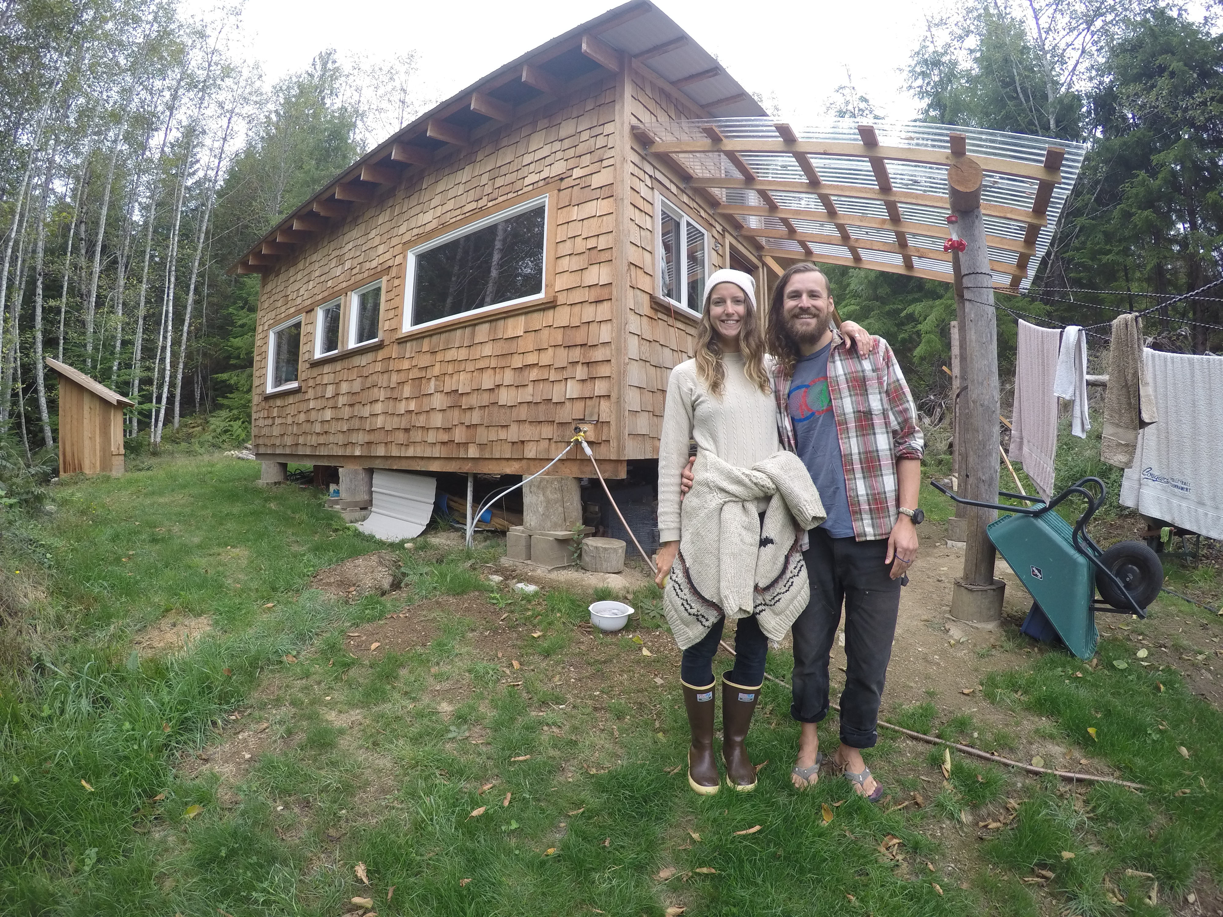 Saxony and Dan in front of his beautiful tiny home on Cortes Island
